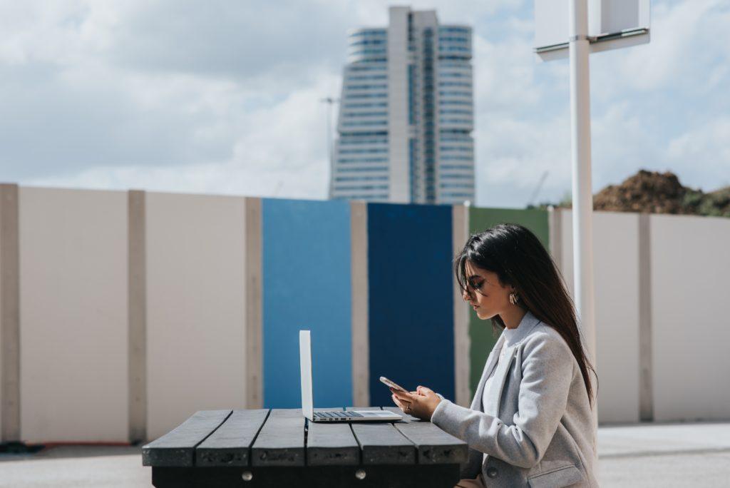 a woman sits outside at a picnic table in front of a laptop while looking at her phone. it looks like the top of a building.