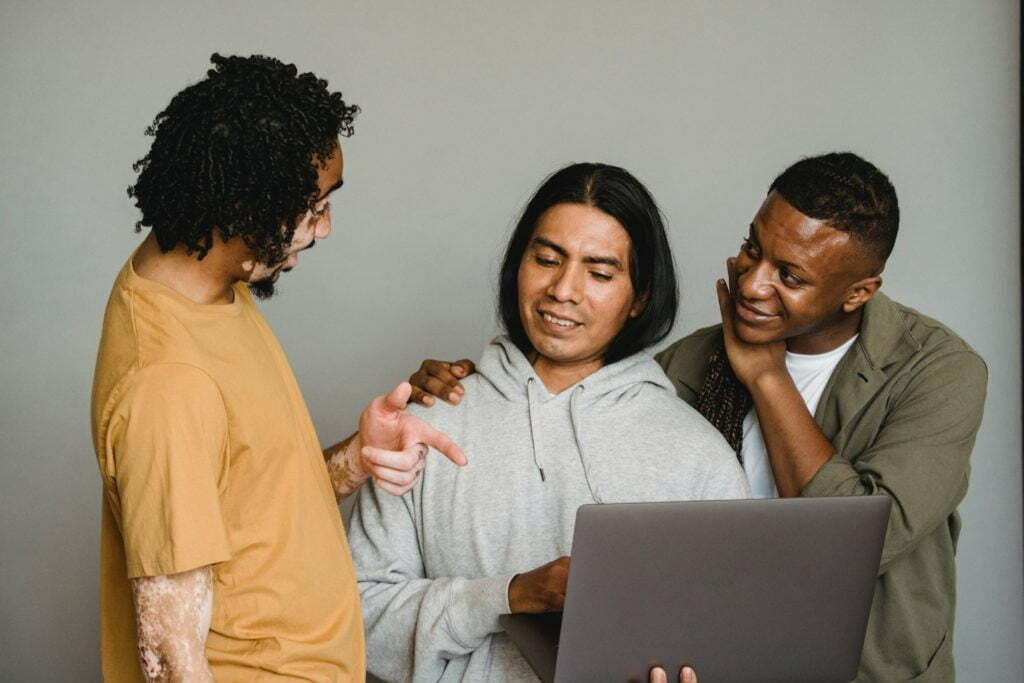 Three men smile and chat while gathered around a laptop