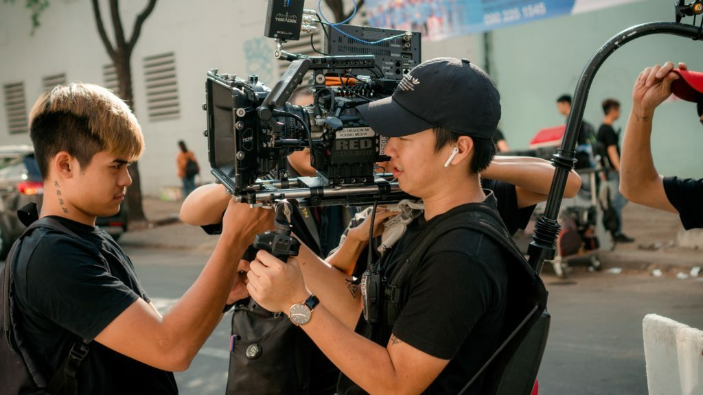 two Asian men hold a large digital camera